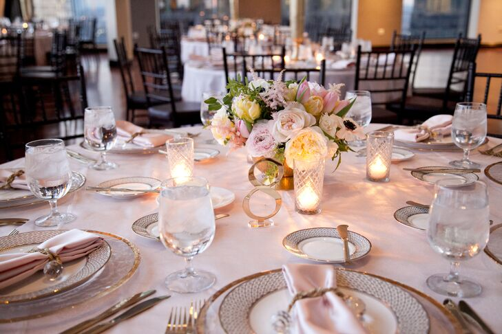 Petalena Flowers created two distinct centerpieces for the reception tables, using sleek architectural vessels to capture the venue's modern appeal. Low centerpieces featured romantic ivory and blush blooms like garden roses, ranunculuses, tulips, astilbes and anemones, with jasmine vine and spirea adding an element of texture to the elegant arrangements.
