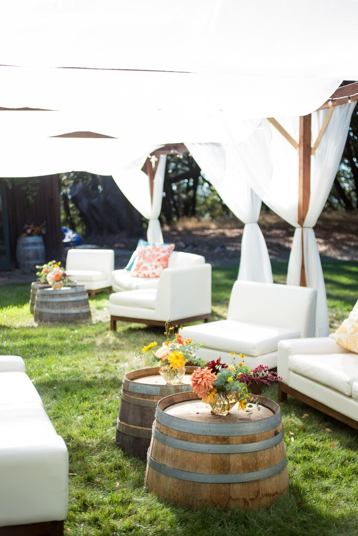 A breezy, shaded outdoor lounge area allowed guests to kick back with a beer or a cocktail after the ceremony. Wine barrels were topped with bundles of bright blossoms.
