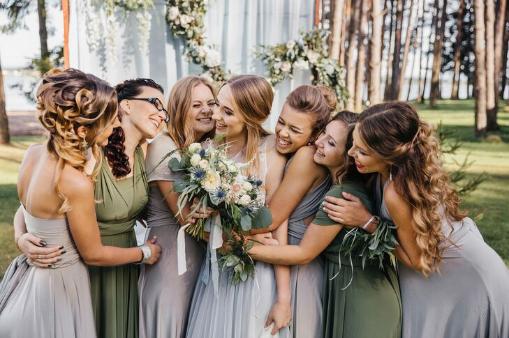 Bridesmaids donned convertible dresses in dark olive and gray that could be styled in a variety of ways, while groomsmen sported light gray pants, vests and knitted ties to match the bridesmaid dresses.