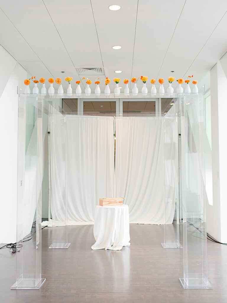 Modern wedding ceremony decor with orange flowers in bud vases