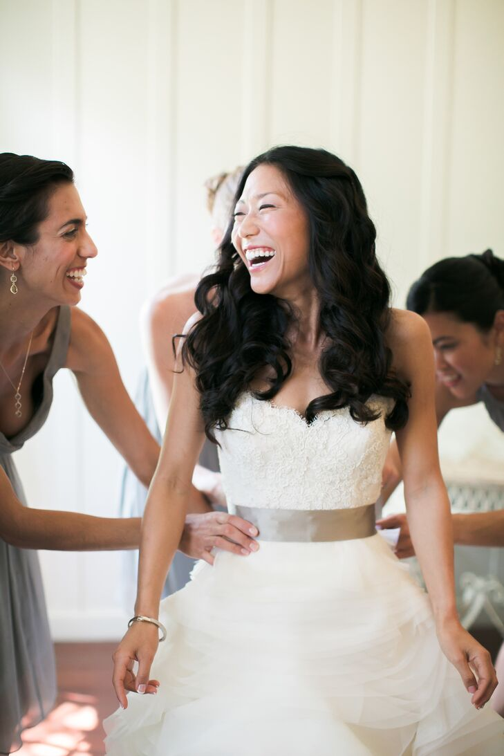 The bridesmaids helped Deborah get ready by helping her into her ivory Lazaro dress with a sweetheart neckline bodice accented in lace. A silver sash wrapped around her waistline, dividing the bodice from the ruffled chiffon skirt