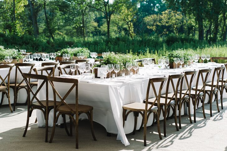 Long, dark wood tables were used to create a communal atmosphere among guests at the outdoor reception. The bride's father even built flower boxes that served as centerpieces while Anna's mom grew the ivy, white euphorbia and bacopa that filled each planter. The natural, simplistic aesthetic was completed using all-white linens and place settings.