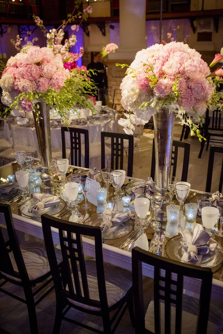 Tall, silver fluted vases filled with pale pink peonies, lisianthus and cascading phalaenopsis and dendrobium orchids topped the rectangular mirrored tables.