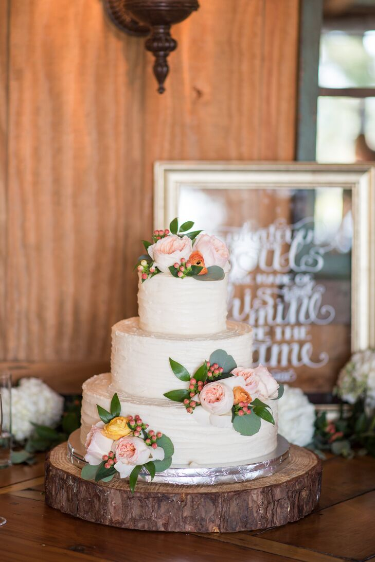 "Morgan and Park's three-tier cake with cinnamon, chocolate and vanilla flavoring was iced in vanilla buttercream frosting and decorated with flowers that complemented the bouquets. Next to the cake, a hand-painted sign read, ""Whatever our souls are made of, his and mine are the same."""