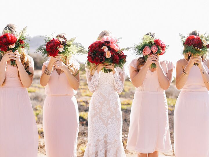 Bride And Bridesmaids Holding Bouquets In Front Of Their Faces