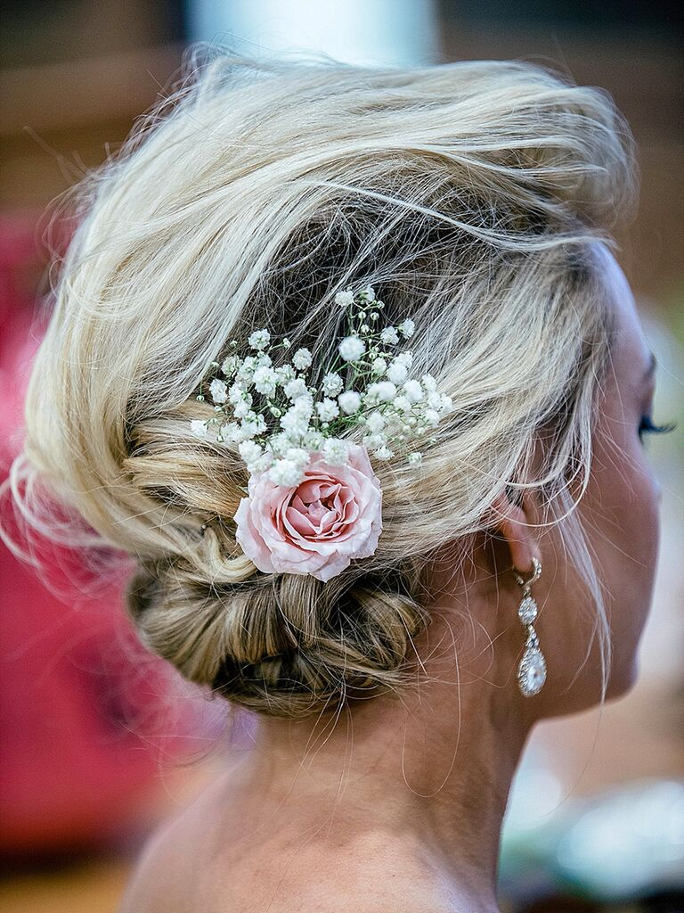 Whispy wedding updo with a rose and baby's breath