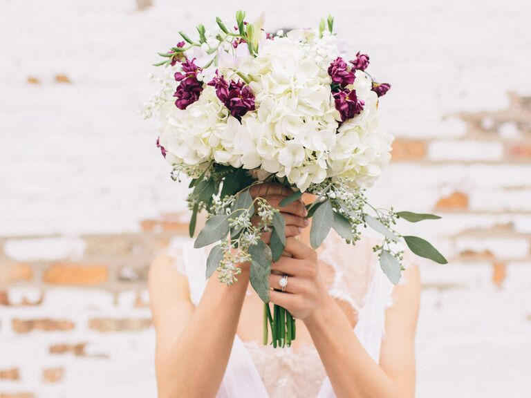 Bride holding an ivory and burgundy bouquet over her face.