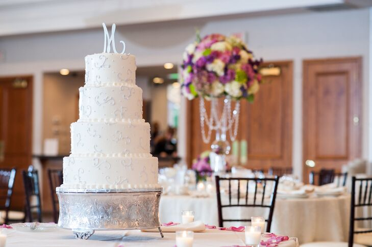 The tall, four-tier wedding cake featured a delicate silver filigree pattern and a silver calligraphic monogram cake topper. After dessert, Tiffany and Ben also served cider and donuts from Blake's Cider Mill (a local orchard) to highlight the season's best treats.