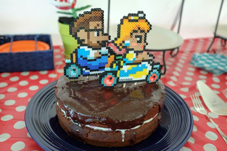 Jacob handmade the perler Mario Kart topper of the couple racing across the chocolate frosted chocolate cake.