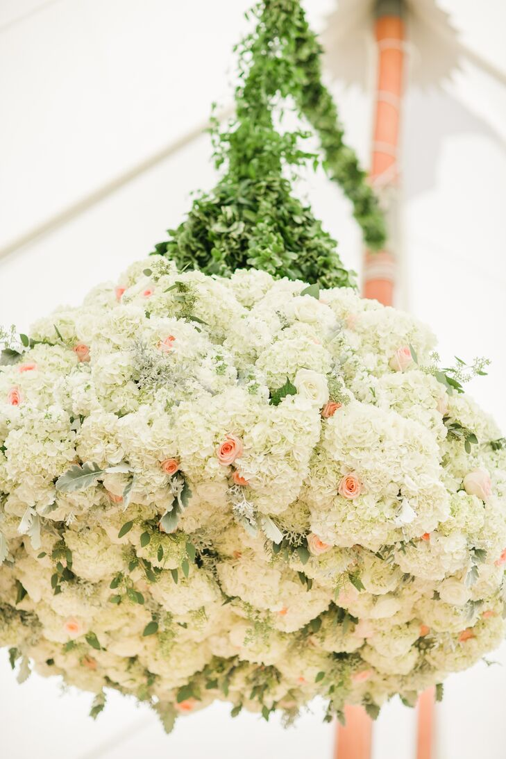 A chandelier arrangement of pink roses mixed in with ivory hydrangeas hung from the tented reception.