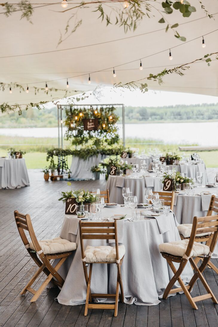 After exchanging vows, the newlyweds celebrated with family and friends with dinner and dancing in a tent overlooking the lake. Tables were cloaked in gray linens and topped with greenery. Romantic bistro lights and greenery were strung across the tent.