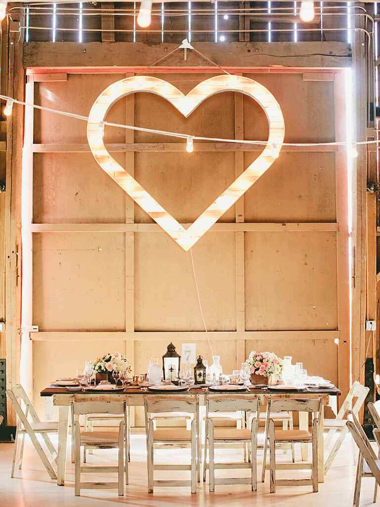 Rustic barn wedding decor with a heart shaped marquee light