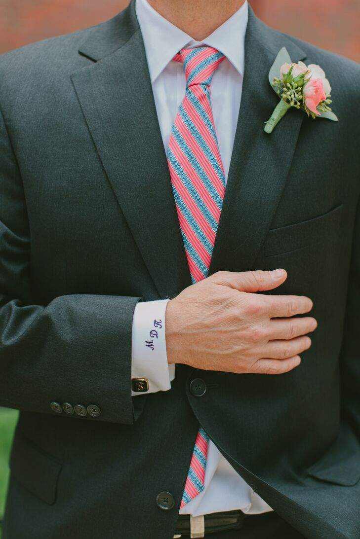 The groom wore a coral spray rose boutonniere. His cuff was monogramed in navy with his initials.