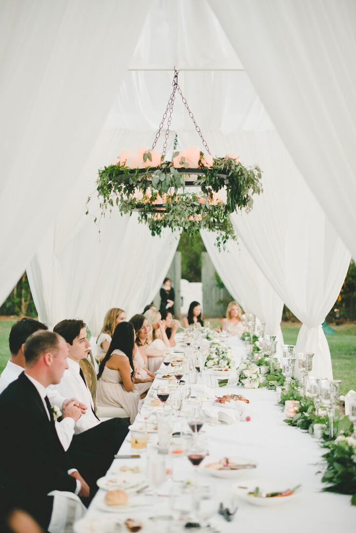 Draping sheer canopies and greenery-wrapped candelabras gave the long head table an air of romance.