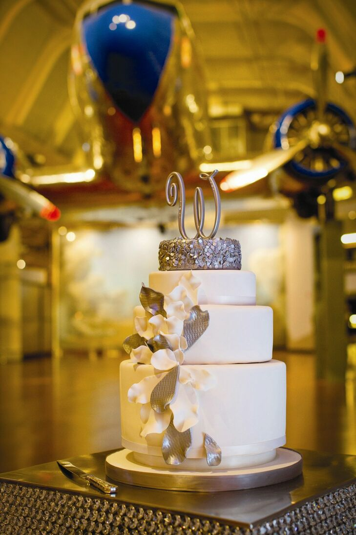 The couple selected a contemporary white and silver fondant cake with an initial topper. The very top layered looked like it was rolled in silver sequence and there were flower petals bursting out of the middle, Tara says.