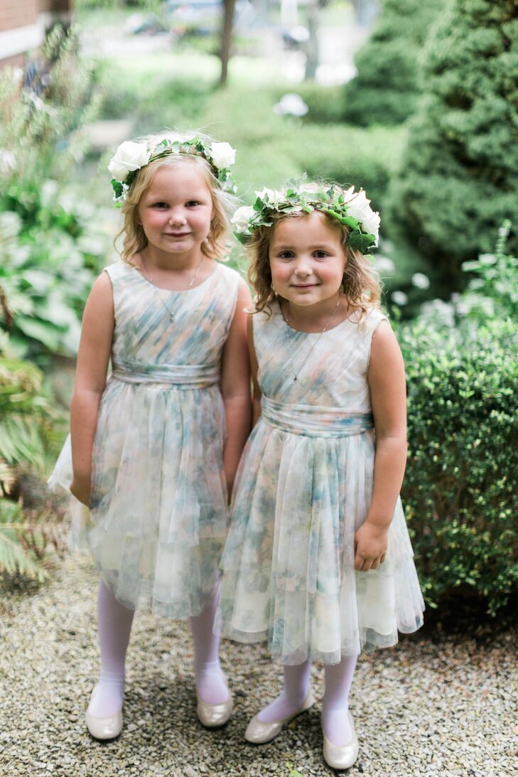 "The flower girl dresses were from the Jenny Yoo flower girl line. ""I loved the dresses because they incorporated the colors of the wedding perfectly—greens, creams and pinks."" The girls also wore wreaths of greenery in their hair, going with the indoor garden theme."