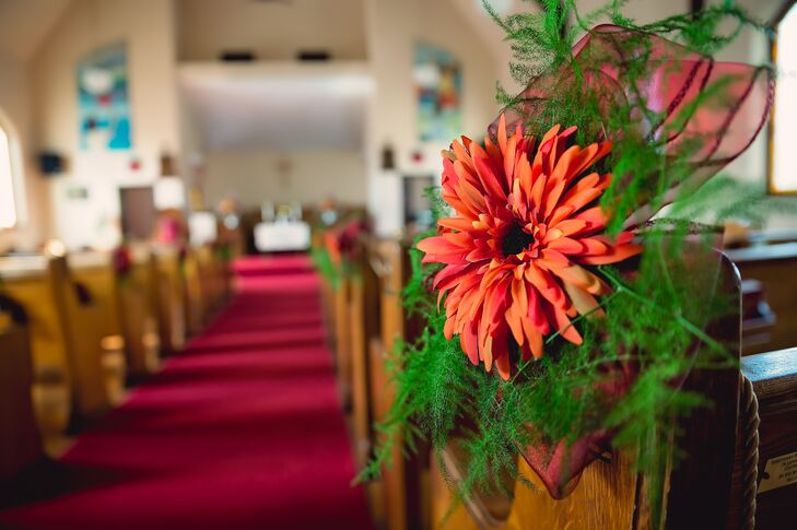 Plush Flowers created simple arrangements of orange gerber daisies with ferns to decorate the pews down the aisle for the ceremony at Walton Memorial Union Church.