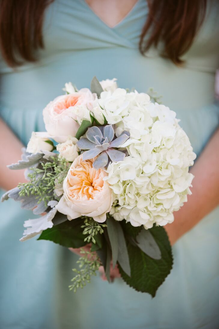 For the bridesmaids' bouquets, Jill opted for a style different than her own, but still had a romantic feel and textured look. Amagansett Flowers by Beth pulled together a summery, cheerful, yet undeniably romantic arrangement of ivory hydrangeas, peach garden roses, seeded eucalyptus, dusty miller and silvery gray succulents.