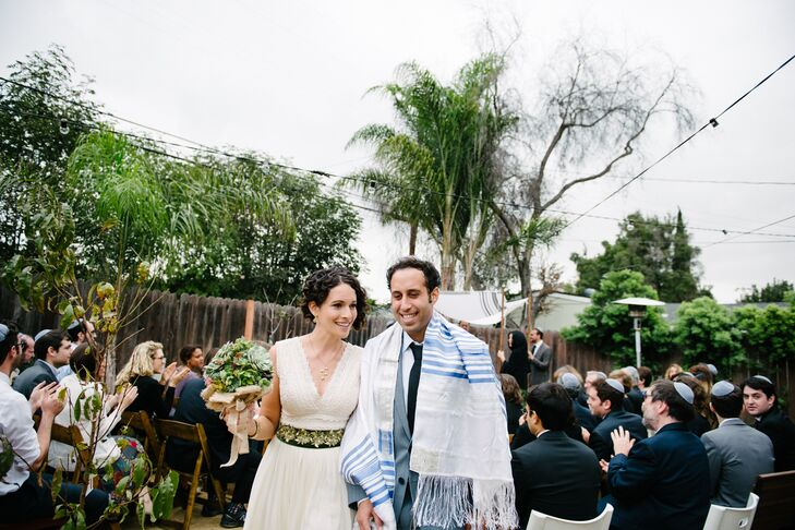 Emily and Chris walked up the aisle after their Jewish wedding ceremony, with the tallith draped around Chris's shoulders. Emily wore a simple necklace and dangling earrings on the wedding day, which accented her ivory dress with a green-fabric flower belt.