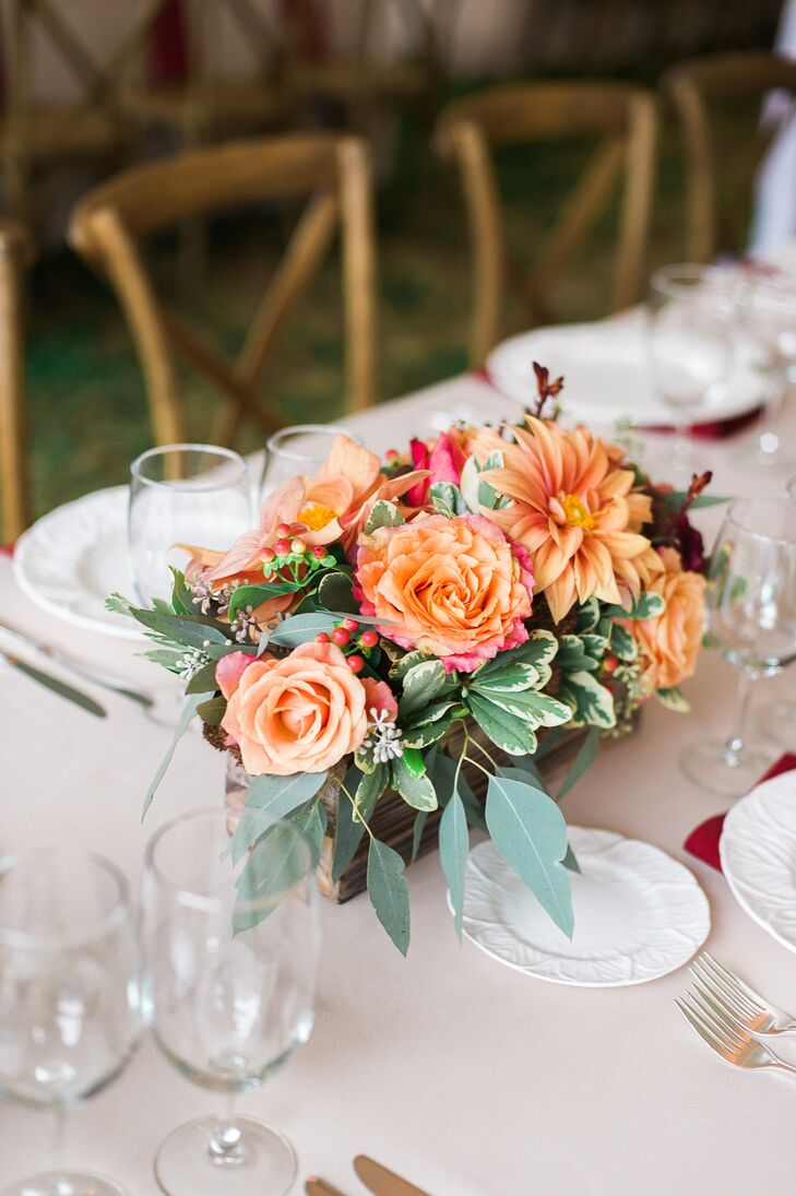 Dining tables had wooden boxes and metal vessels filled with peach roses and dahlias decorating the middle, along with a bed of greenery at the bottom. Other flower arrangements that decorated the reception included succulents, hydrangeas and a variety of herbs.