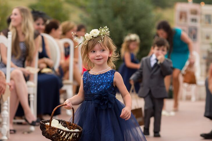 The flower girl wore a sparkly navy tulle dress with a rose and baby's breath flower crown. She carried a wicker basket and threw white rose petals down the aisle.