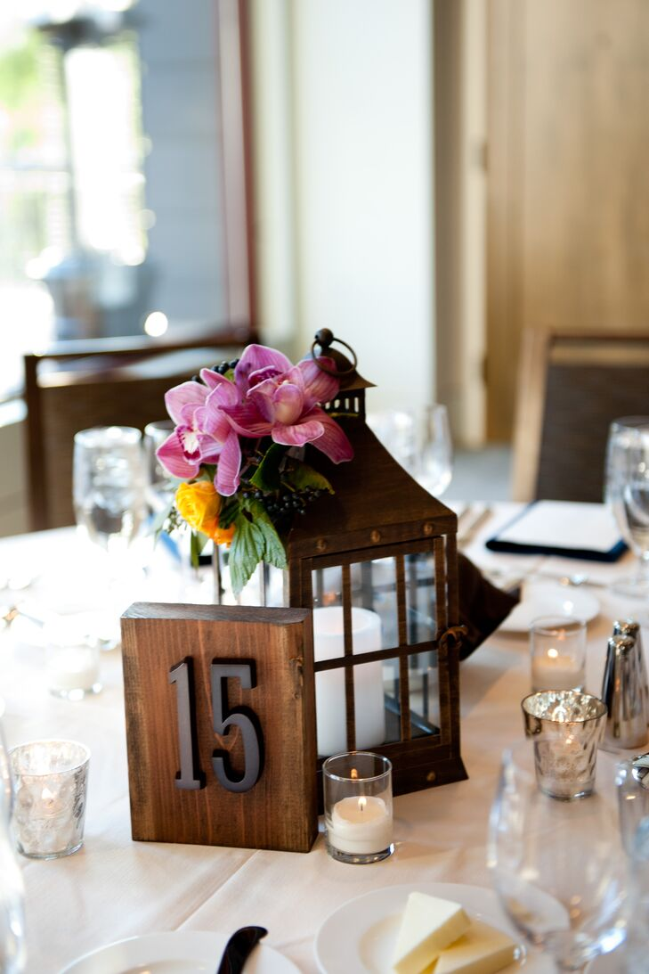 Rustic lanterns, pink orchids and orange roses decorated the reception tables. rn