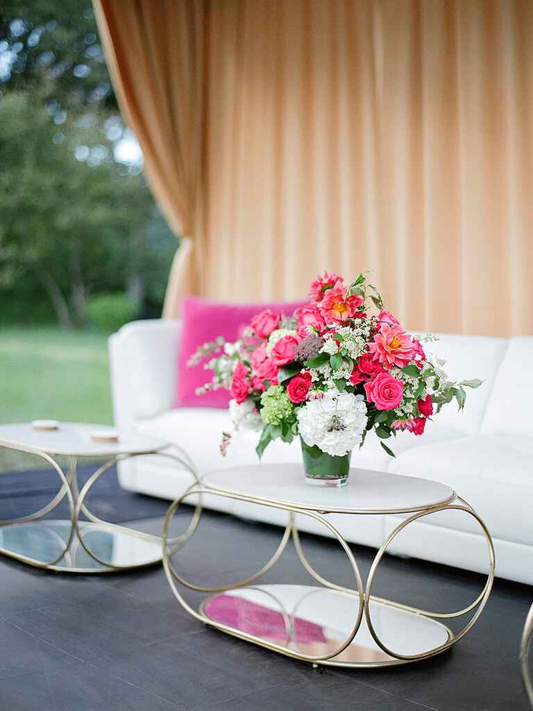 Outdoor wedding tented lounge area with bright flowers