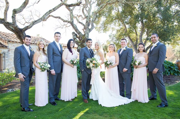 "The couple stood with their wedding party, who wore blush and charcoal gray that followed the larger color palette of blush, ivory, gold, gray and accents of lace. ""My bridesmaids all wore blush-colored luxe chiffon dresses, all with different necklines that were suiting for each bridesmaid,"" Jamie says. ""The groom and groomsmen all wore Vera Wang slim-fit charcoal gray tuxedos."""