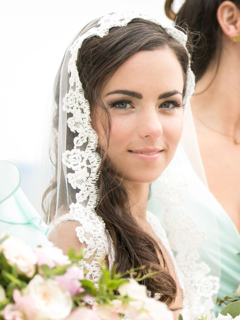 A bride who looks like Kate Middleton looking at the camera