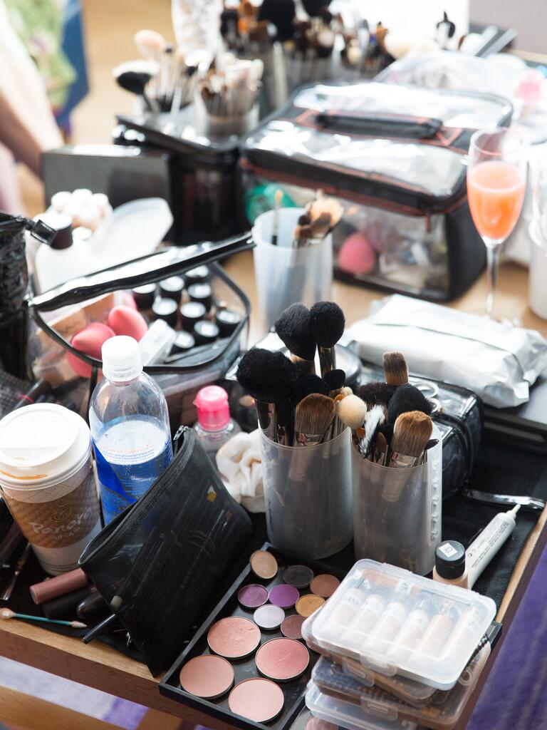 Wedding day makeup table with lots of makeup and Bellinis in champagne glasses
