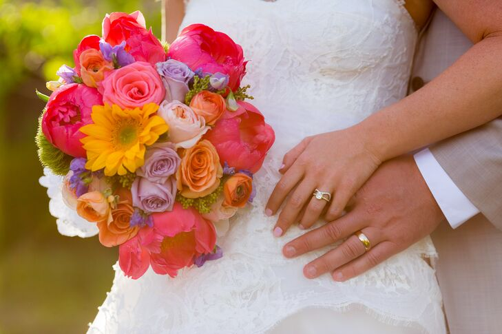 Katie carried yellow daisies; pink peonies; orange ranunculus and pink, orange and purple roses in her bouquet.