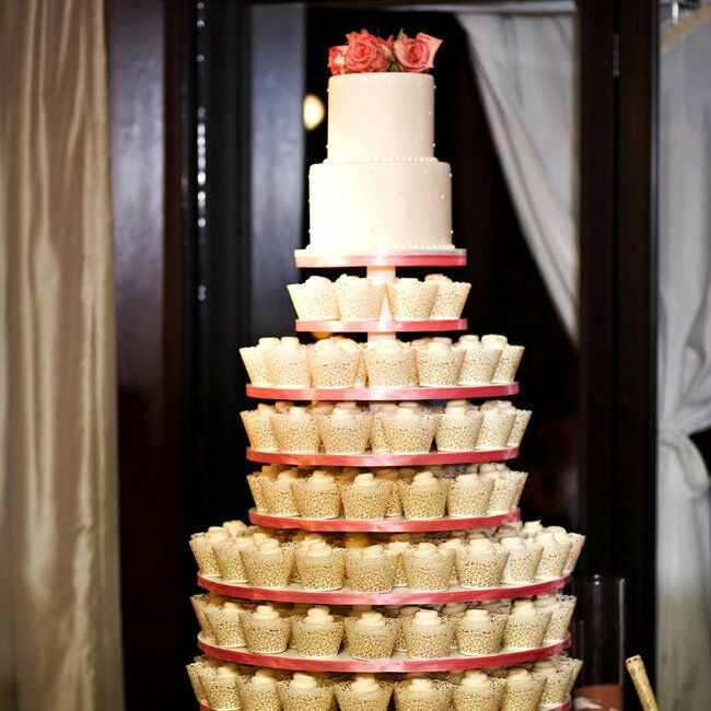 Eight tiers of vanilla cupcakes in lace-cut paper created the base for Dorothy and Mark's two-layer buttercream cake.