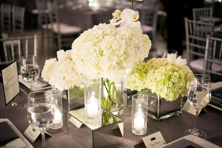 Dining tables had a range of high and low centerpieces filled with ivory blooms, including this arrangement of lush hydrangeas. White candles in glass cylinder vases and mirror boxes added additional romance to the centerpieces.