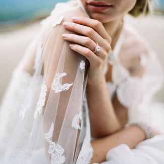 Bride with lace veil and diamond engagement ring
