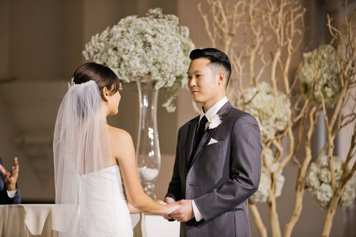 Ken held Stephanie's hands at the front of the altar during the ceremony, wearing a gray suit with a black tie. He had a single orchid boutonniere pinned to his jacket lapel, which went along nicely with Stephanie's overflowing orchid bouquet, both arranged by Lotus and Lily.