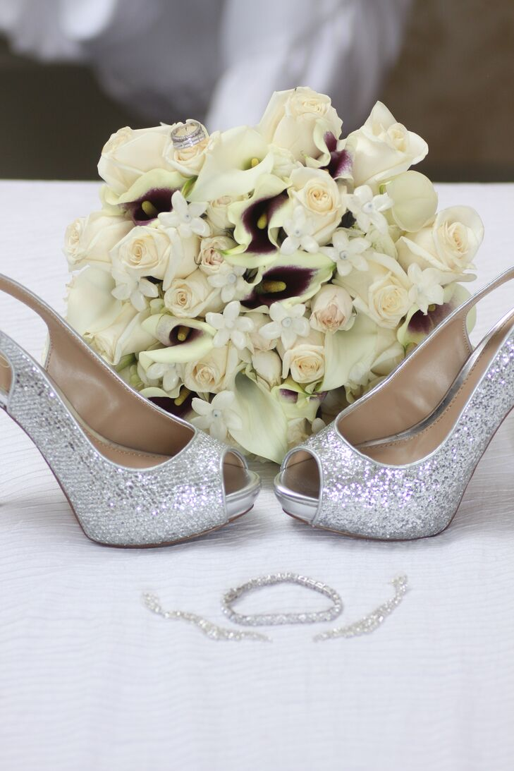 Mayowa accessorized her white wedding dress with a pair of sparkly silver peep-toes to match her silver jewelry. She carried a White rose and calla lily bouquet with pops of deep purple in a color palette to signify riches and royalty.