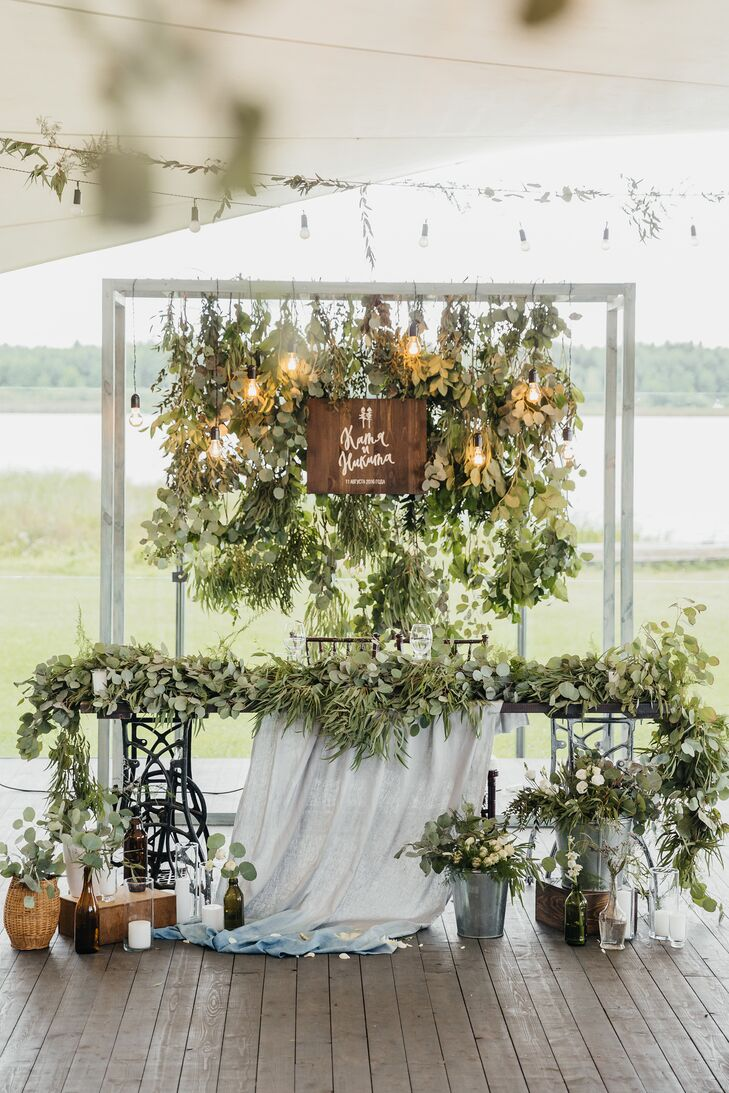 Katya and Nikita's romantic sweetheart table at Shishki Hotel in Zagorshchnya, Belarus, was draped in etherial linens and decorated with lush greenery.