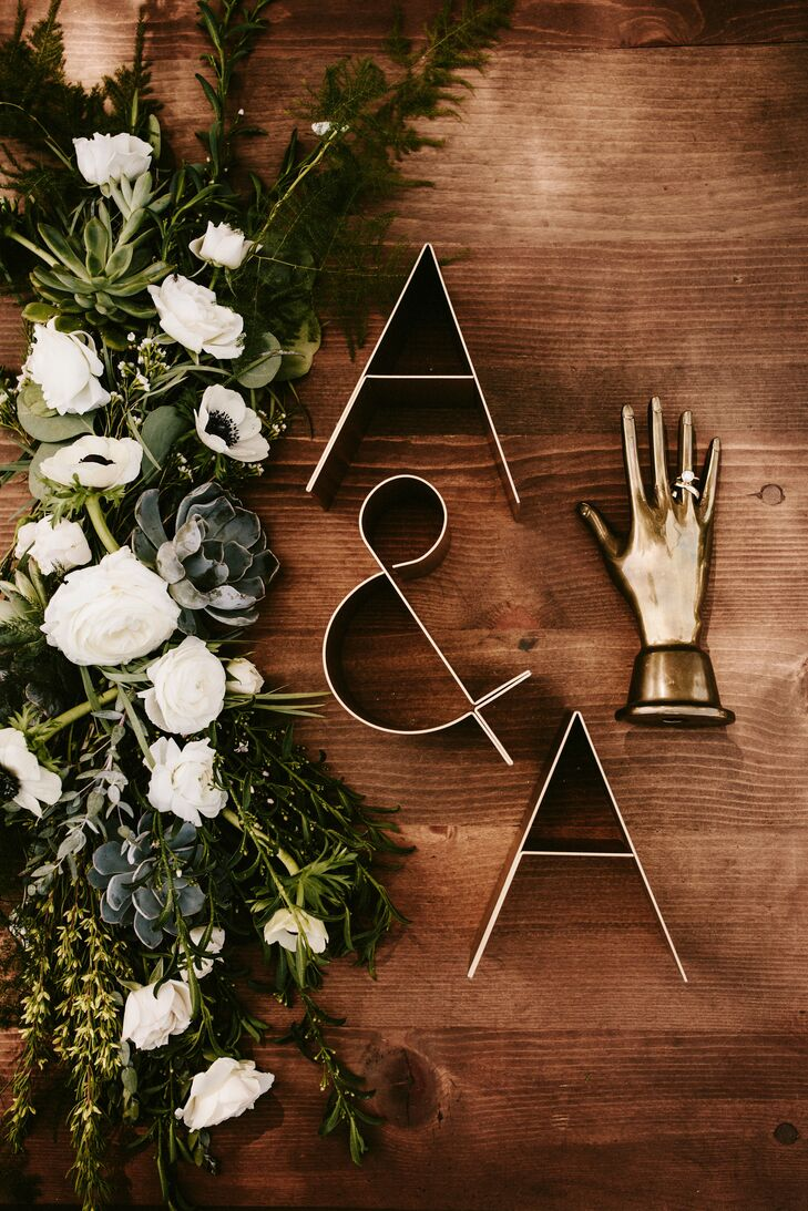At the reception at Frederick Loewe Estate in Palm Springs, California, tables were topped with greenery-rich garlands filled with native desert plants like succulents and grasses. Anna and AJ's table was topped with special bronze monogram letters.