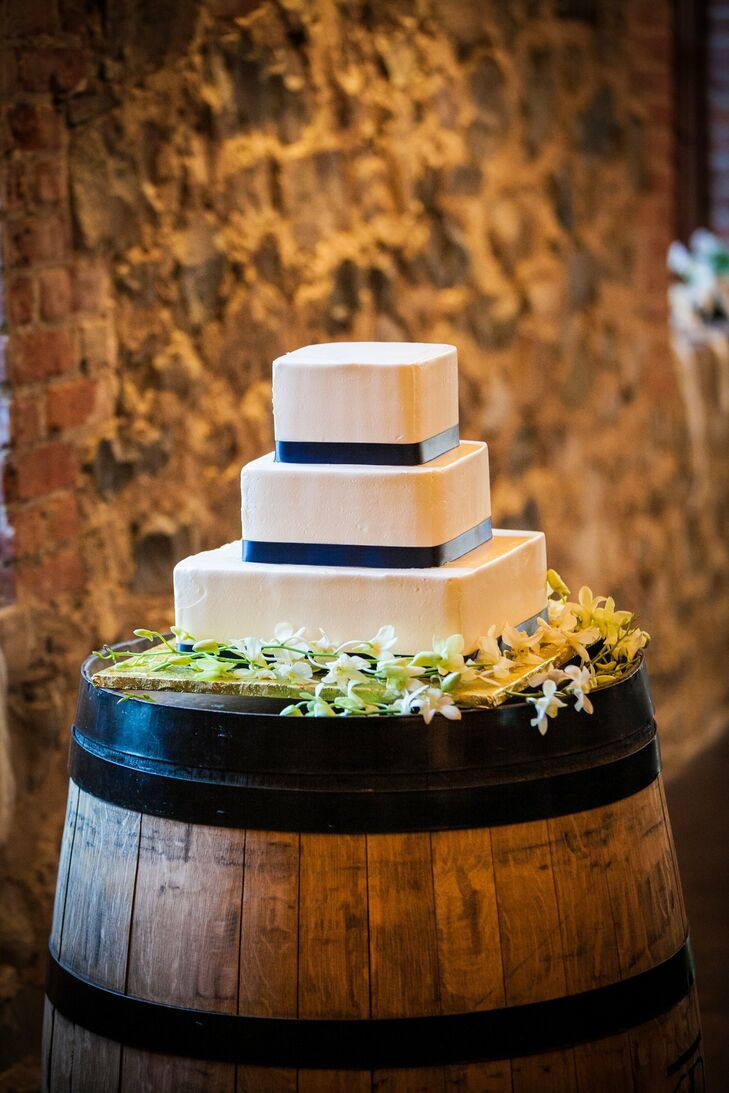 The couple chose a modern square style for their wedding cake, which was frosted with white buttercream frosting and accented with navy ribbon.