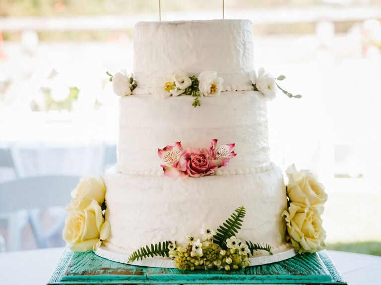 White textured buttercream wedding cake with garden topper