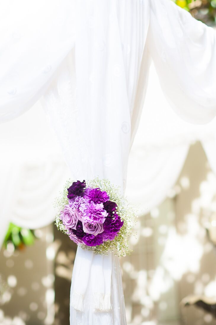 white draped chuppah with purple flower decor