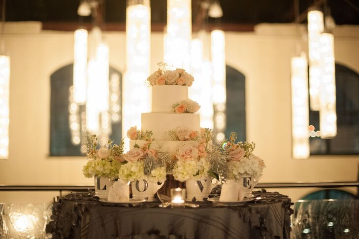 "The white wedding cake at the reception was created by Clay's Creative Corner Bakery. It was decorated with pink roses, ivory hydrangeas and baby's breath. Small flower arrangements on the cake table filled ceramic mugs that spelled out ""Love."""