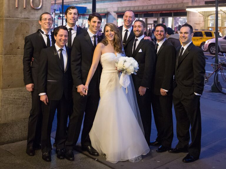 Bride poses with groomsmen at Manhattan wedding