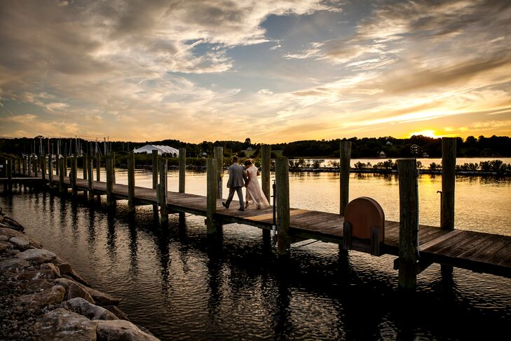 The married couple walked down the dock at sunset along the Chesapeake Bay.