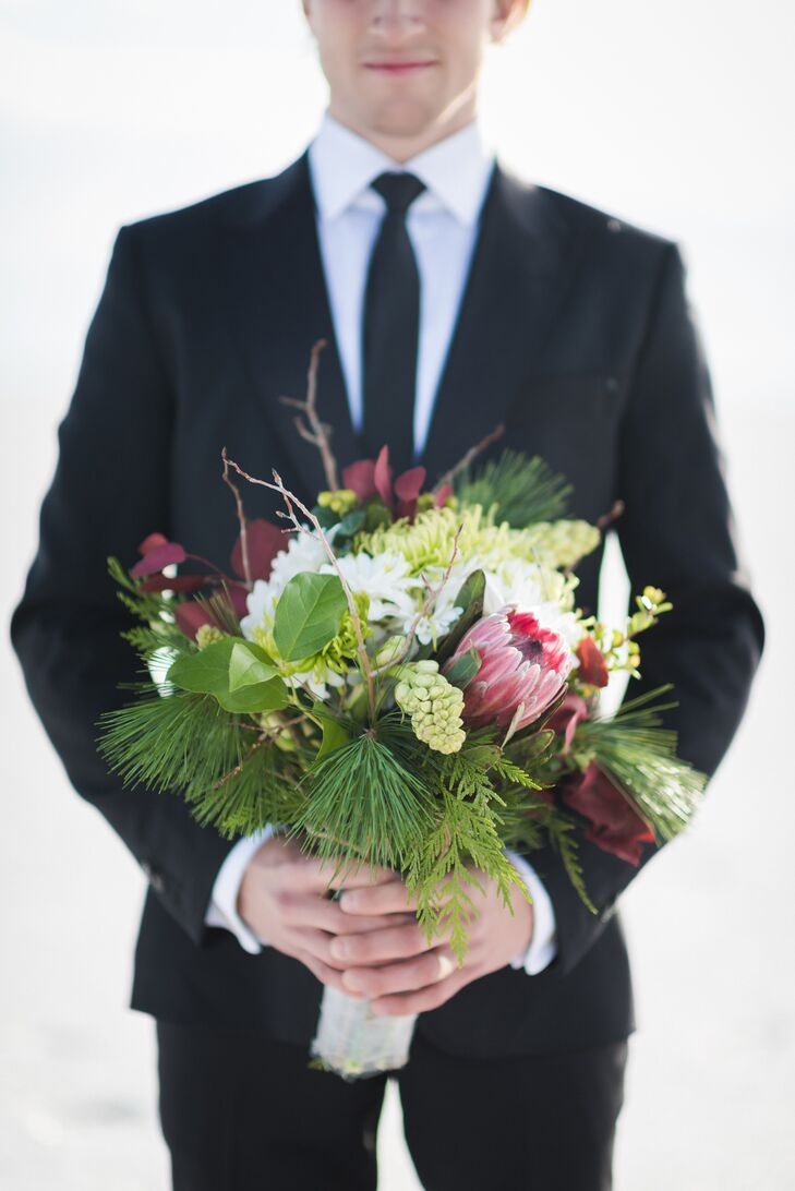 Heather's bouquet included bold pops of reds and greens that stood out against the winter landscape. The arrangement included evergreen sprigs with red eucalyptus and a king protea.