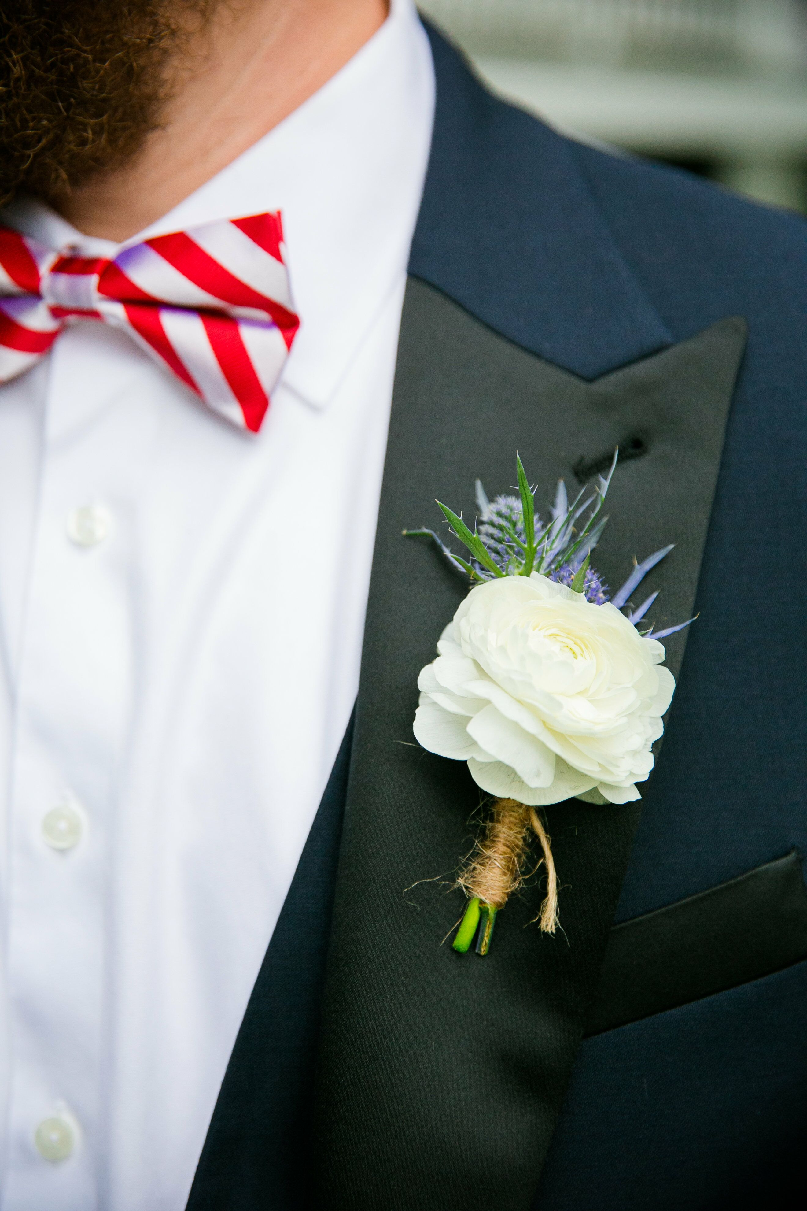 white ranunculus  blue thistle groomsmen boutonniere