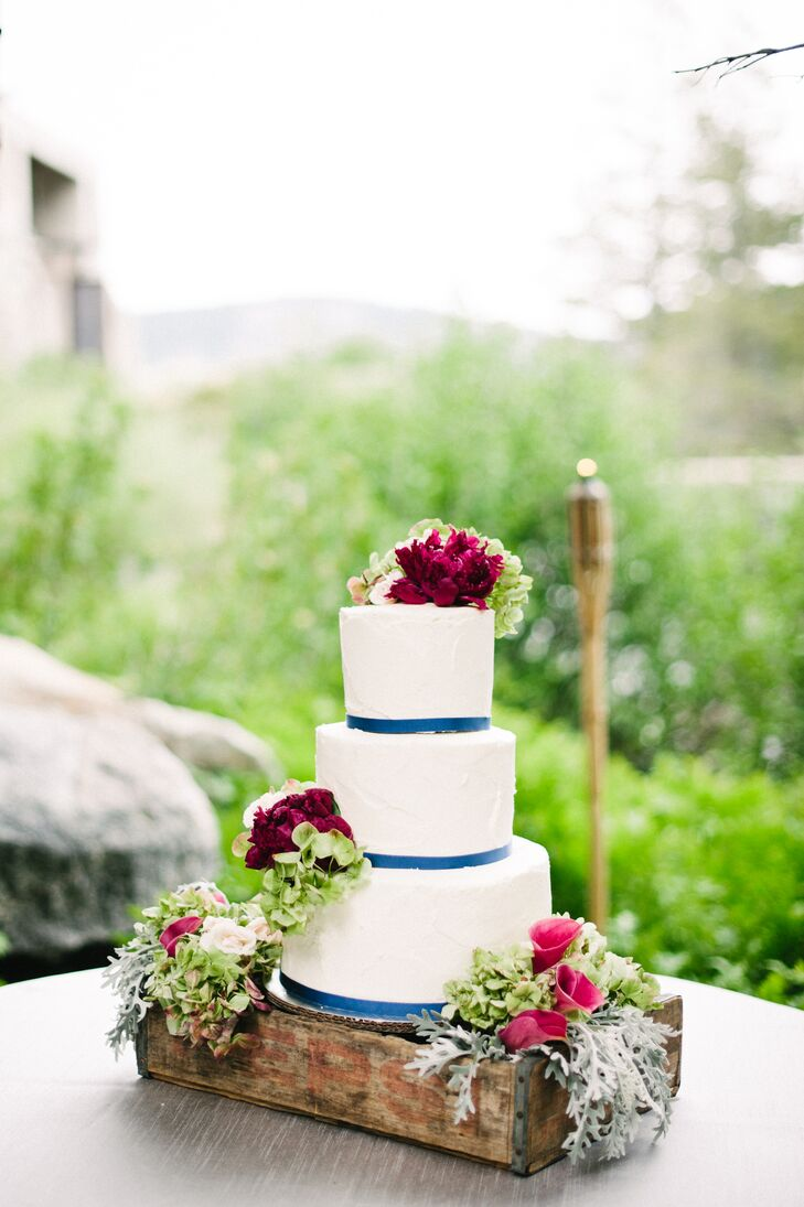 The white wedding cake was wrapped at the base of each tier and was accented with a variety of fresh flowers that matched the day's color palette. The cake was filled with coconut, chocolate mousse and carrot-cake flavors, which was created by Cake Tahoe.