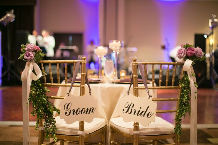 Amanda and Chris's gold chiavari chairs had hanging bride and groom signs with lavender ribbon. Lavender spray roses and jasmine vines on opposite ends set their seats apart from the rest.