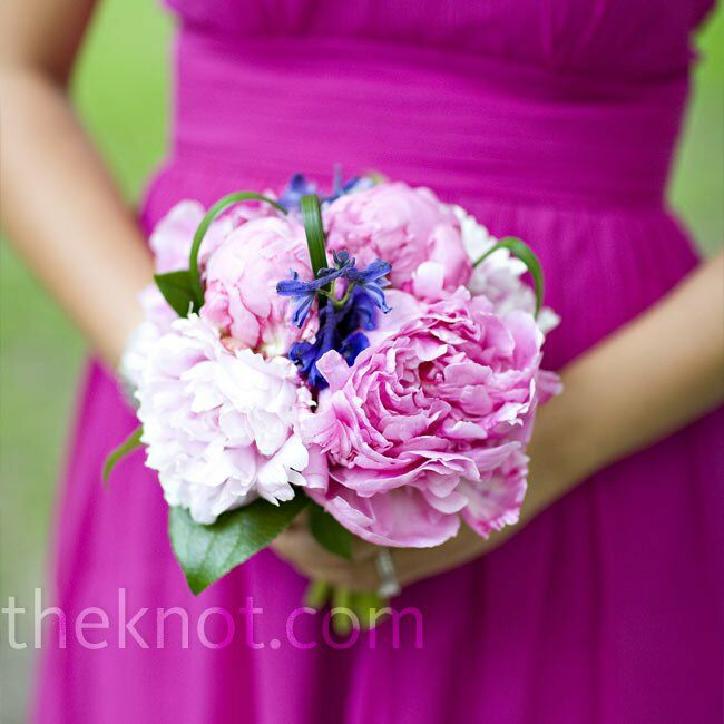 "Kelly loves peonies, and when she found out the bridesmaid dress color she and the girls had picked was called ""wild peony,"" she took it as a sign. Her bridesmaids carried bouquets of fuschia peonies with deep blue delphiniums."