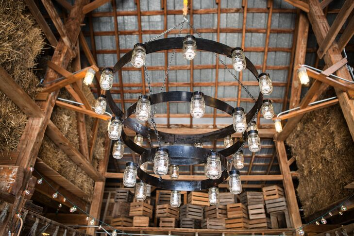 Black-iron chandeliers, made of lightbulb-filled mason jars, illuminated the space inside the barn. Other rustic touches included wooden crates, square hay bales and wooden beams.
